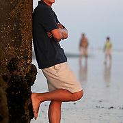 A man enjoys the view at Huntington Beach as the sun sets over the Pacific Ocean.