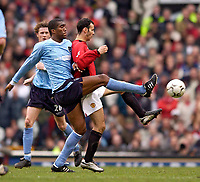 Photo. Jed Wee.<br /> Manchester United v Manchester City, FA Barclaycard Premiership, Old Trafford, Manchester. 13/12/03.<br /> Manchester City's Sylvain Distin (L) stretches out a leg to win the ball from United's Ryan Giggs.