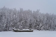 A Sea Nymph flat bottomed boat waits along the riverbank, covered in snow, for spring to return