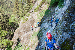 Group of people climbing steep rock face via ferrata towards Stuibenfall Waterfall, Otztal, Tyrol, Austria