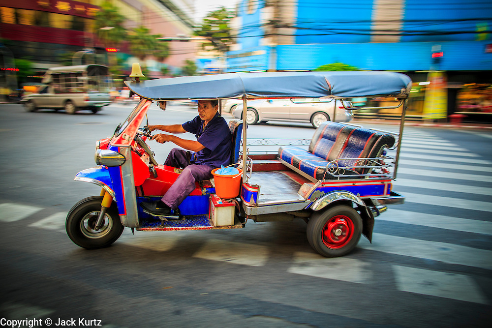 07 DECEMBER 2012 - BANGKOK, THAILAND:  A tuk-tuk (three wheeled taxi) in traffic in the Chinatown section of Bangkok, Thailand. Chinatown is the entrepreneurial hub of Bangkok, with thousands of family owned businesses selling wholesale merchandise in everything from food like rice, peanuts and meats, to dry goods like toys and shoes. Tuk-tuks are three wheeled taxis that use a motorcycle engine. In one form or another they are common in much of Asia.     PHOTO BY JACK KURTZ