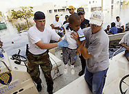 A boy of a staffer at United Medical Rehabilitation Hospital is lifted into a boat after he was rescued from the flooded hospital in New Orleans East August 31, 2005. Authorities struggled on Wednesday to evacuate thousands of people from hurricane-battered New Orleans as food and water grew scarce and looters raided stores, while U.S. President George W. Bush said it would take years to recover from the devastation. REUTERS/Rick Wilking