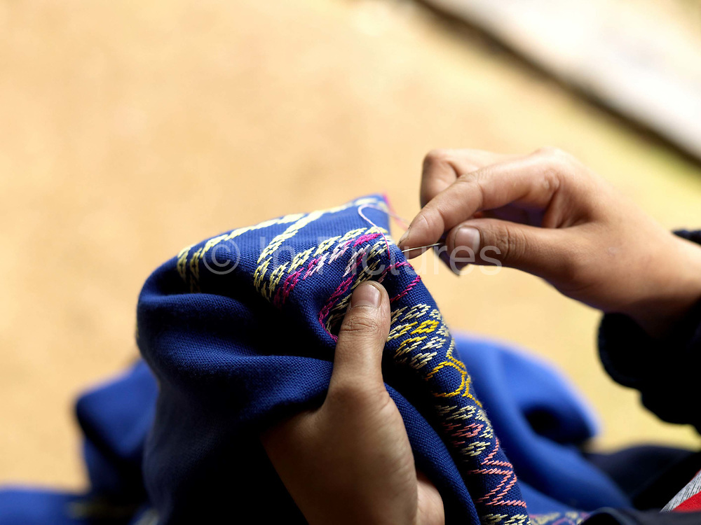 In the school holidays, a young Tai Dam girl embroiders her first sinh (Lao traditional skirt), Ban Na Mor, Oudomxay province, Lao PDR. She has been watching and learning from her mother and other female family members since she was a young child.