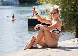 © Licensed to London News Pictures. 07/08/2020. London, UK. Hannah Kent 25 from Twickenham enjoys a cooling drink in the sunshine next to the River Thames at Richmond in South West London as temperatures are expected to reach to 35c today. Thousands of sun seekers have flocked to parks, rivers and the south coast as temperatures soar with beaches and roads becoming jammed with holidaymakers. The heat is set to continue for the rest of the week with temperatures expected in the high 20s. Photo credit: Alex Lentati/LNP