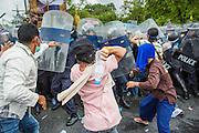 24 NOVEMBER 2012 - BANGKOK, THAILAND: Anti government protesters battle Thai riot police during a large anti government, pro-monarchy, protest  on November 24, 2012 in Bangkok, Thailand. The Siam Pitak group, which sponsored the protest, cited alleged government corruption and anti-monarchist elements within the ruling party as grounds for the protest. Police used tear gas and baton charges againt protesters.       PHOTO BY JACK KURTZ