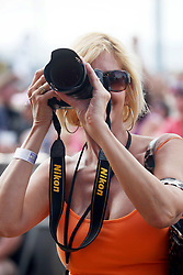 27 April 2012. New Orleans, Louisiana,  USA. .New Orleans Jazz and Heritage Festival. .A lady in the crowd taking photos of singers on stage..Photo; Charlie Varley.