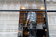 A man wearing a chequered shirt stands in the window of a retailer in Mayfair whose angular Georgian-era architecture is in the background, on 29th April 2021, in London, England.