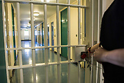 An officer unlocks the corridor gate in Beaufort House, a skill development unit for enhanced prisoners. Part of HMP/YOI Portland, a resettlement prison with a capacity for 530 prisoners.Dorset, United Kingdom.
