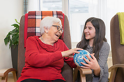 Girl playing bowling with senior woman in rest home