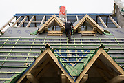 A workman balances on the tile supports of a new Polish house's roof, on 16th September 2019, in Zakopane, Malopolska, Poland.