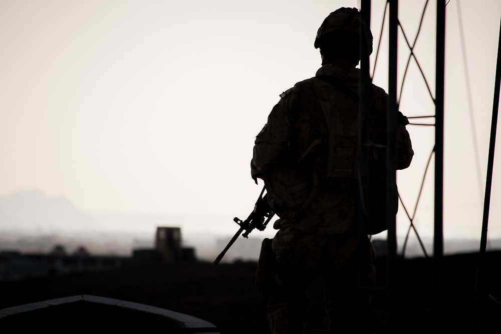 The section's gunner, private Petitclerc, stands watch on the roof of Kandahar University over the suburbs during a patrol in December 2007.