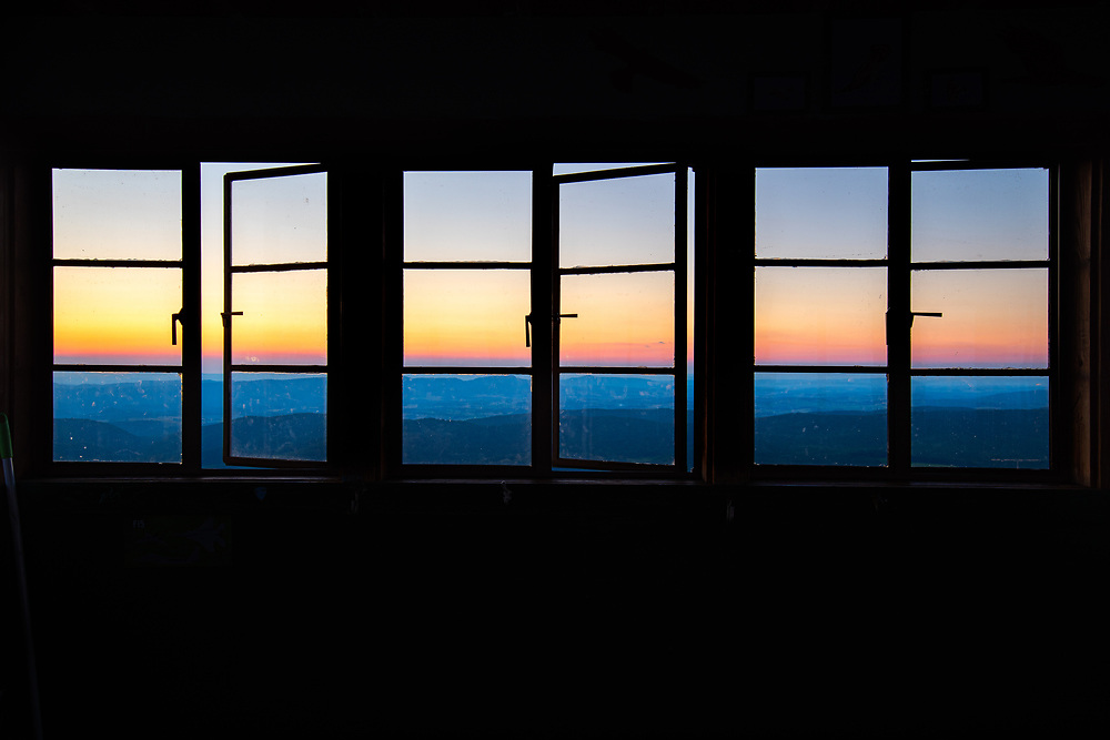 The distant West Virginia mountains are viewed from inside the old fire tower at the Hanging Rock Raptor Observatory below the firey colors of sunset.