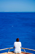 Woman in her twenties looks out at an endless expanse of calm blue ocean