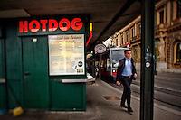 View of a man walking past a hot dog (Wienerschnitzel) stand, Vienna, Austria.