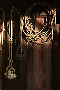 Detail of traditional riding equipment in shaft of sunlight, Estancia La Bamba De Areco, Pampas, Argentina, South America