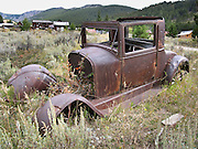 An old car body, shot with bullet holes, missing its engine, rusts in Elkhorn State Park, Montana, USA.