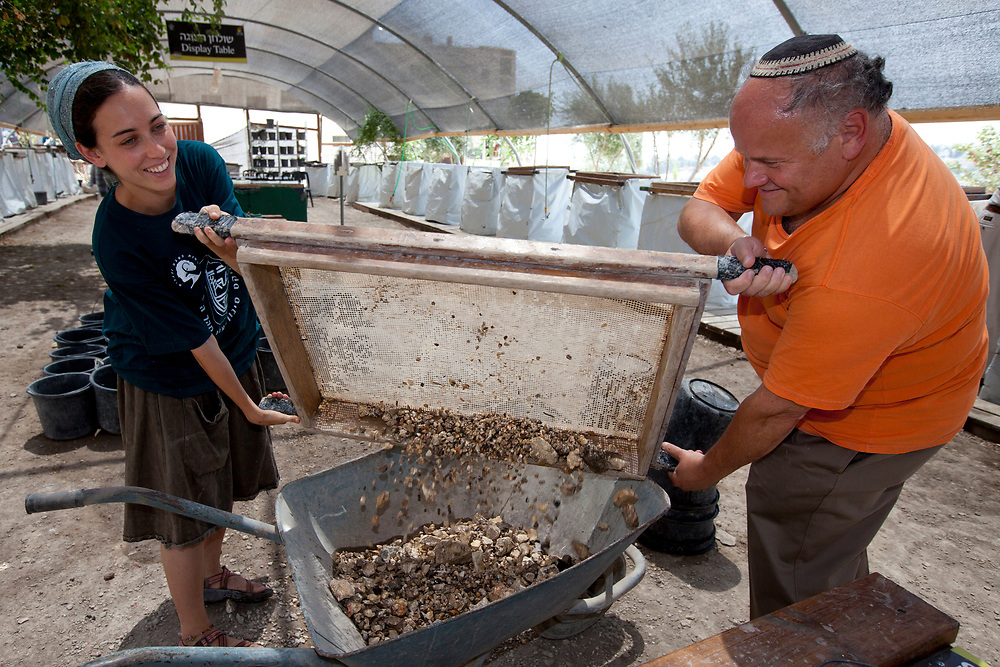 An instructor (L) helps a visitor to pour dirt and debris to a wheelbarrow at the Emek Zurim wet-sieving facility site, located on the mount of olives in Jeursalem, on August 3, 2010. In 1999, the Muslim waqf, responsible for preservation of holy sites on the Temple Mount, began construction on the south-east side of Temple Mount, at a site known as Solomon's Stables. Despite objections by leading archaeologists, claiming that this would inflict irreparable archaeological damage to the site; the construction continued, and vast amounts of dirt and land were removed from the Temple Mount. The Temple Mount Antiquities Salvage Operation, led by archeologists Prof. Gabriel Barkay and Zachi Zweig, is currently engaged in sifting through the 600 tons of dirt and land from the site. This project, operated under the auspices of the City of David, is located in nearby Emek Zurim National Park. The salvaged findings continue to astound visitors with discoveries dating back to the First and Second Temple Periods.