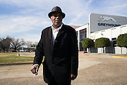 """MONTGOMERY, AL – JANUARY 25, 2016: Michael Harris, 52, walks to his car outside the new Greyhound station on South Boulevard. In 2011, the downtown Montgomery Greyhound bus station was converted into a museum to honor the freedom riders, who endured a violent attack there in 1961. The replacement bus station, located four miles from downtown, is a prime business opportunity for independent cabbies like Michael Harris, who make a living serving passengers unwilling to rely on city buses. Many characterize the public bus system in Montgomery as unsafe and unreliable, so wary passengers cough up $2 per mile for trips in Mr. Harris' 2005 Lincoln Navigator, traveling across town for fast food, or sometimes as far as New York City. """"This is my life,"""" Harris said. """"I love driving, and I help people out. It's just in my heart."""""""