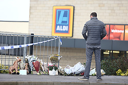 © Licensed to London News Pictures. 22/12/2017. Skipton, UK. A man looks at the flowers left at the scene where a 30 year old woman has died after she was stabbed in an Aldi supermarket in Skipton. North Yorkshire Police have arrested a 44 year old man on suspicion of murder following the attack shortly before 3:30 pm on Thursday. Photo credit: Andrew McCaren/LNP