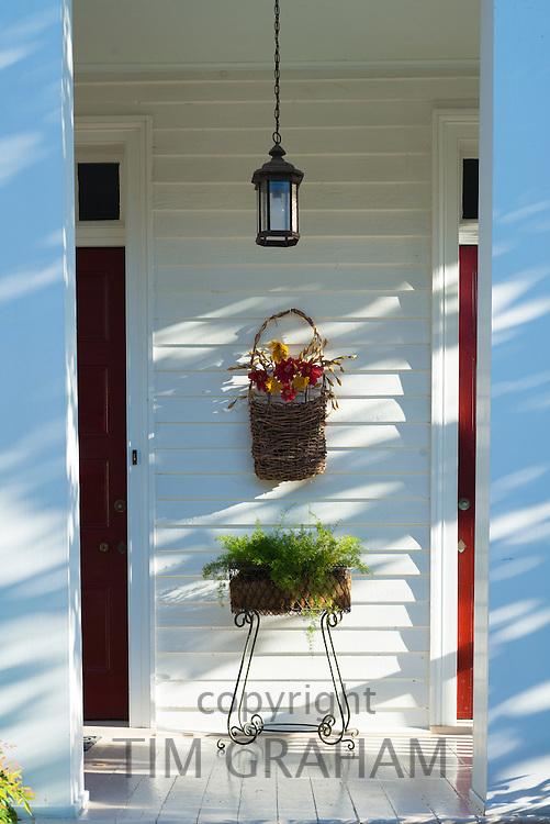 Hanging basket floral display on stoop of stylish clapboard house in Natchez, Mississippi, USA