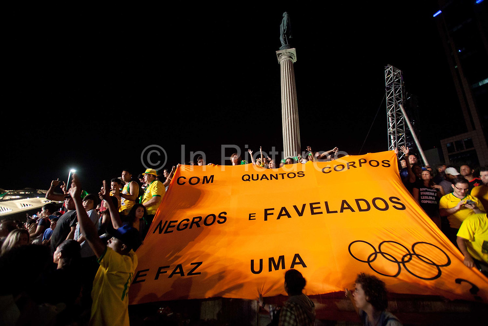 How many black and favela peoples bodies deaths does it take to make an Olympics banner protest at the Brazil-Germany football match, live site Praca Maua. Thousands of Brazilians and some foreigners watched the Brazil vs Germany Olympic football final match in Praca Maua, on the Olympic boulevard, Rio de Janeiro, celebrating Brazis victory, in what could be regarded as a revenge match after Germany beat them 7-1 in the same Maracana Stadium in 2014.
