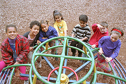 Multiracial group of children playing on roundabout in playground,