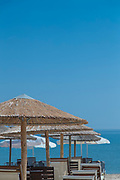 Sunshades and deckchairs at beach under clear sky, Chios town, Chios, Greece