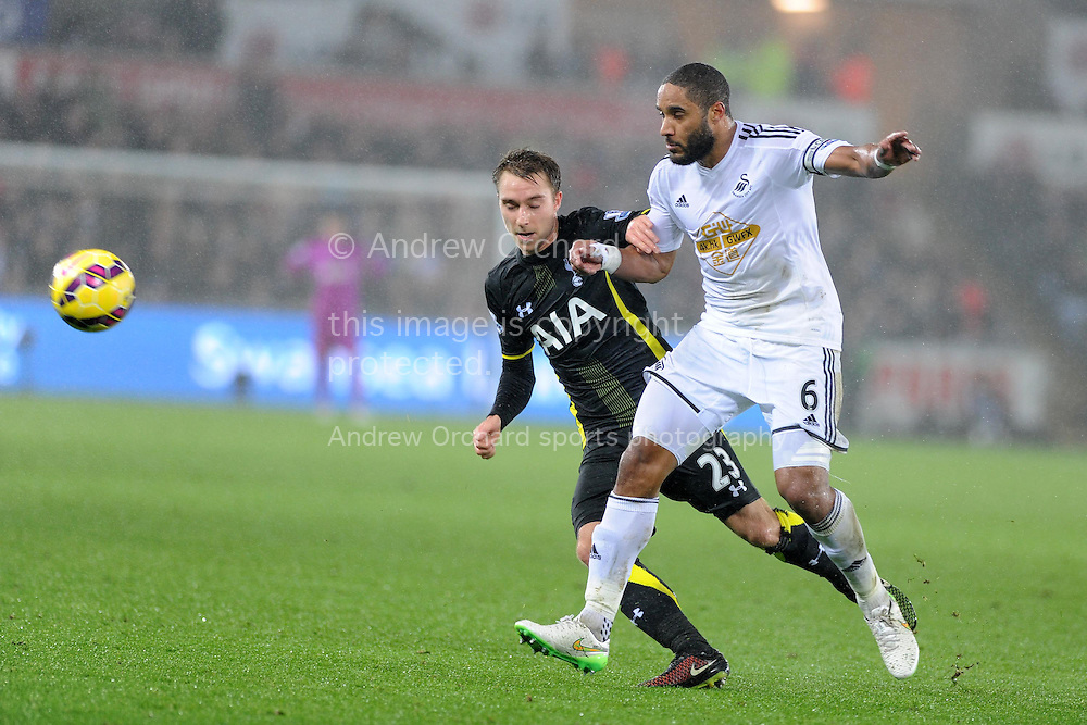 Christian Eriksen of Tottenham (l) is tackled by Ashley Williams of Swansea city.  Barclays Premier League match, Swansea city v Tottenham Hotspur at the Liberty Stadium in Swansea, South Wales on Sunday 14th December 2014<br /> pic by Andrew Orchard, Andrew Orchard sports photography.