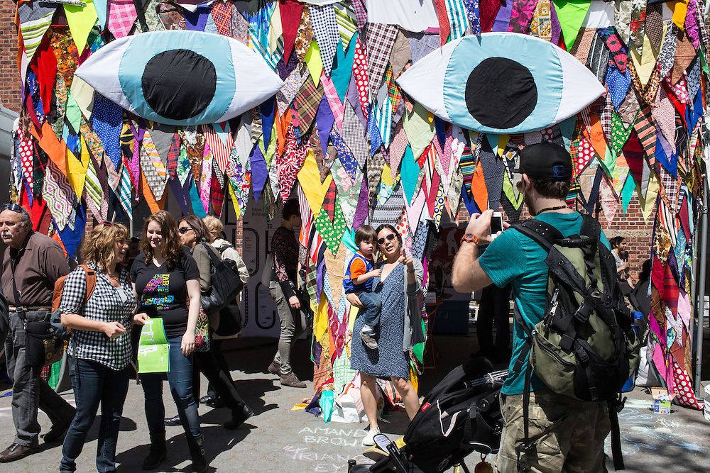 Bystanders pose for photos in front of an exhibit decorated with triangles of fabric and featuring two large eyes.