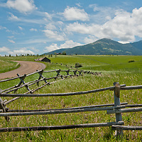Fair weather cumulus clouds drift over pastures in Montana's Gallatin Valley, near Bozeman. Mount Ellis and the souther Gallatin Range rise in the background.