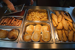 Trays of pies; chips; sausages and other fat saturated food in school canteen,