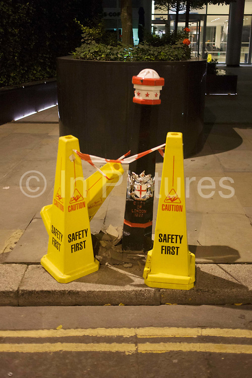 A detail of Health and Safety cones, taping off a broken City of London bollard. Three plastic cones, taller than the traffic versions, stand on the kerbside near double-yellow no parking lines. The tape joins them together as a pointless gesture, adhering to exaggerated H&S safety laws. Passing pedestrians are urged to exercise caution in case they trip and sue the borough.