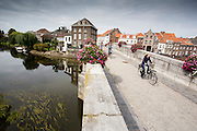 In Roermond rijden fietsers over de Maria Theresiabrug over de Roer. De brug wordt ook wel de Stenen brug genoemd en is gebouwd in 1771.<br /> <br /> Cyclists riding at the Maria Theresia Bridge in Roermond. The bridge is also known as the Stenen Brug and is built in 1771.