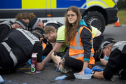 © Licensed to London News Pictures. 20/09/2021. Welwyn Garden City, UK. Protesters having their hands removed form the road. Protesters from Insulate Britain attempt to blockade the A1M junction 4 near Welwyn Garden City, Hertfordshire. Climate change activists Environmental protest group Insulate Britain have successfully blocked traffic at various points of the M25 on several occasions over the past week. Photo credit: Ben Cawthra/LNP