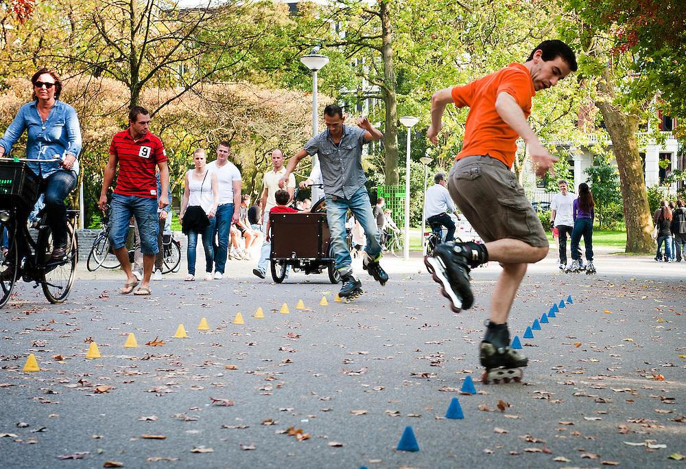 Nederland, Amsterdam, 25 sept  2011.Inline skaters in het Vondelpark hebben een parkoers uitgezet van kleine pilonnetjes waar ze omheen skaten. Meestal doen ze dat razendsnel, voor of achteruit..Foto (c): Michiel Wijnbergh