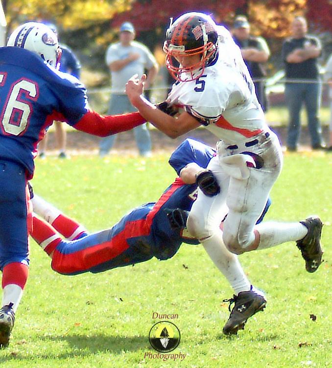 "October 20, 2007 -- TOPSHAM, Maine. Brunswick Junior Quarterback Robbie Basquez evades two Mt. Ararat tacklers in Saturday's win in Topsham. Brunswick won the ""Battle of the Bridge"" 26-15. Photo by Roger S. Duncan."