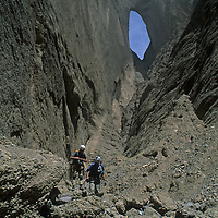 CHINA, Xinjiang. Expedition (MR) in slot canyons below huge Shipton's Arch in arid Kara Tagh Mts. near Taklimakan Desert.