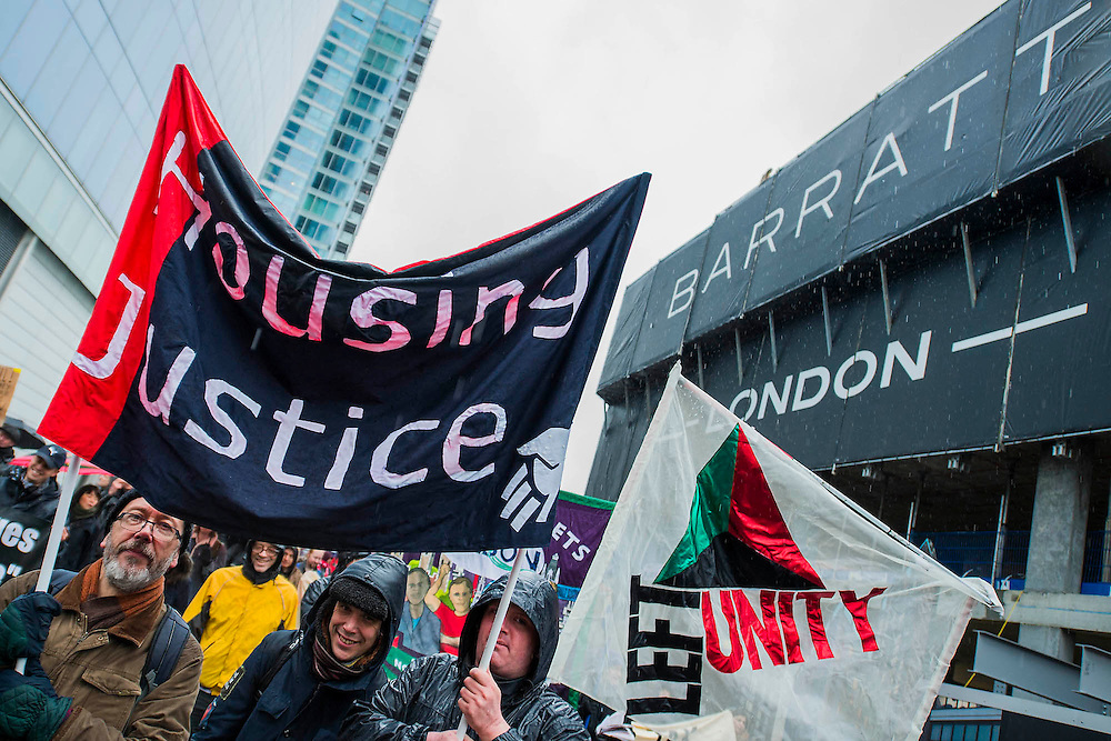 Here, passing a luxury Barrat development at Aldgate. People marched from South London and East London to City Hall to demand better homes for Londoners and an end to the housing crisis. Demands included rent controls, affordable and secure homes for all, an end to the Bedroom Tax and welfare caps and the building of new council houses. The event was called by Defend Council Housing and  South London People's Assembly. And the East London route started at Parish Church of St. Leonard, Shoreditch, London, United Kingdom. 31 Jan 2015.Guy Bell, 07771 786236, guy@gbphotos.com