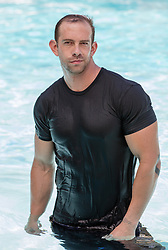 muscular man in a wet tee shirt standing in a swimming pool