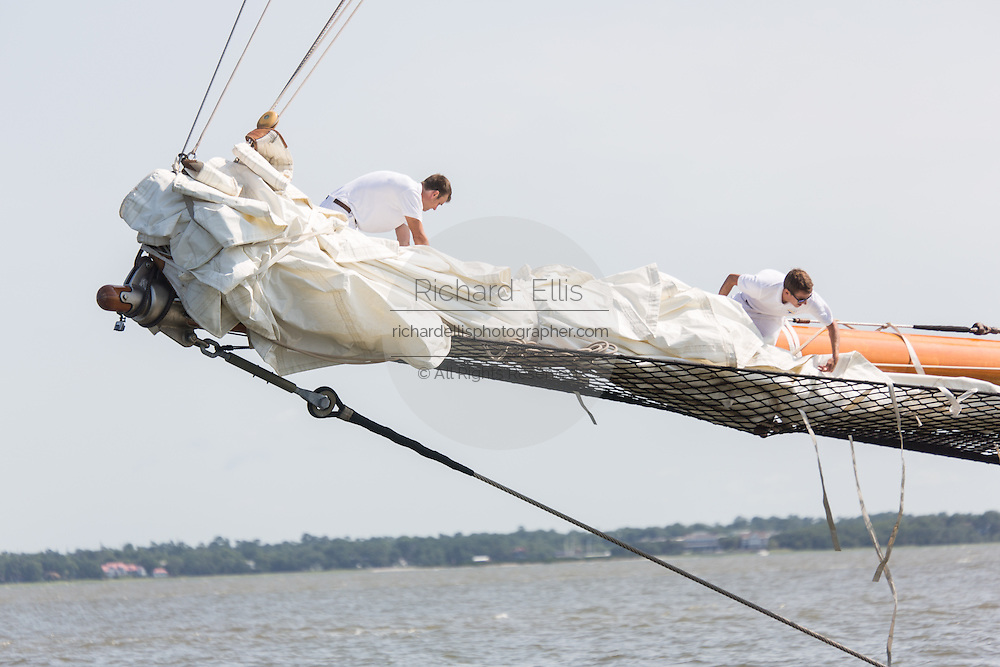 Deck hands rig the sails on the 196-foot sailing yacht Germania Nova as it sails Charleston Harbor June 26, 2013 in Charleston, South Carolina.