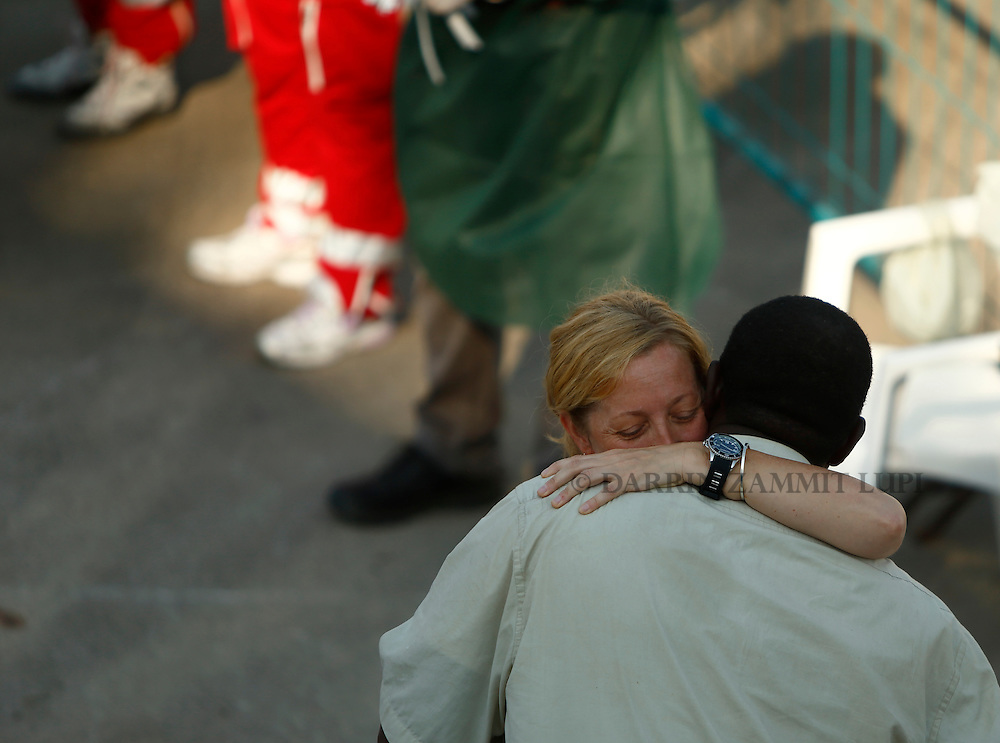 A migrant and the Medecins san Frontiere (MSF) team leader embrace as migrants disembark from the MSF rescue ship Bourbon Argos in Trapani, on the island of Sicily, Italy, August 9, 2015.  Some 241 mostly West African migrants on the ship arrived on the Italian island of Sicily on Sunday morning, according to MSF.<br /> REUTERS/Darrin Zammit Lupi <br /> MALTA OUT. NO COMMERCIAL OR EDITORIAL SALES IN MALTA