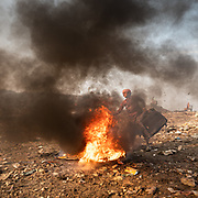 A woman burns old luggages to collects metal in it. Located next to a lake, a visit to one of the main garbage dump in Kolkata. With 15 millions population in 2019 and growing, the city of Calcutta is a typical case of expansion through uncontrolled urbanization.<br /> Calcutta, India