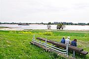 Nederland, Andelst, 23-4-2019Op en langs de dijk wandelen en fietsen mensen in de zon. Het is  mooi voorjaarsweer . Een binnenvaartschip vaart voorbij. Typisch hollands landschap van het rivierengebied .Foto: Flip Franssen
