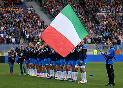 Italy players stand near a large flag during the national anthem before the NatWest 6 Nations match at the Stadio Olimpico, Rome.