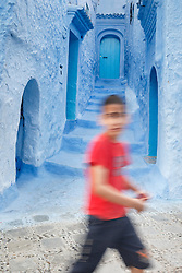 Boy walking past blue walls and staircase, Chefchaouen, Morocco