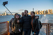 A family group of tourists pose and smile for a selfie photograph at the back of Staten Island Ferry travelling away from Lower Manhattan, which can be seen in the background,Upper Bay, New York City, New York, United States of America.