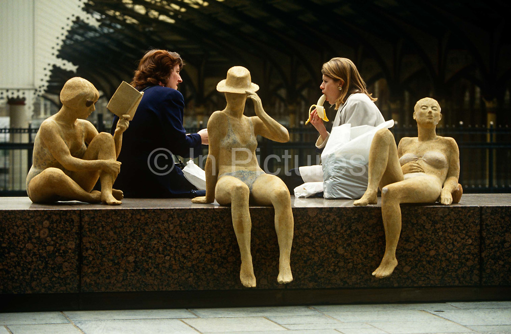 Female colleagues enjoy a chat over an alfresco lunch in the city alongside an art installation of women at the beach. Rather suggestively we see, one lady eating a fresh banana to suggest a sexual act but this is in the open air at one of the City of London's financial district's landmarks, Broadgate that is adjacent to Liverpool Street Station whose arched Victorian roof is seen in the background. The scene is of the female gender, taking a well-earned break from office life, while perhaps, dreaming of and planning their next holiday vacation on a tropical beach. The working women and their leisurely counterparts are juxtaposed from an unknown artist's installation in London. The banana, by its very curved shape has long been the butt of sexual innuendo and double-entendre. The surrogate penis being the perfect adult pun.