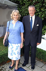 MR MICHAEL & LADY ANGELA OSWALD at a garden party at the Goring Hotel, Beeston Palce, London SW1 to celebrate the unveiling of a bronze bust the late Queen Elizabeth the Queen Mother on 20th July 2004.