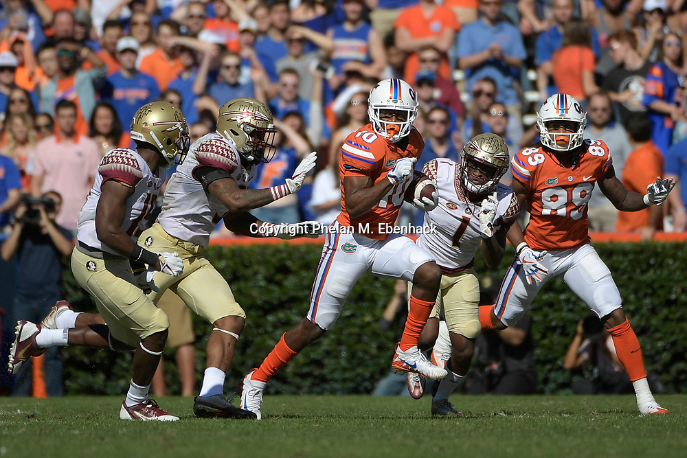 Florida wide receiver Josh Hammond (10) runs after catching a pass in front of Florida State defensive back A.J. Westbrook (19), defensive back Derwin James (3) and defensive back Levonta Taylor (1) during the first half of an NCAA college football game Saturday, Nov. 25, 2017, in Gainesville, Fla. (Photo by Phelan M. Ebenhack)