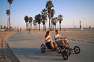 Young tourist couple tandem cycling along palm tree lined path next to beach at sunset, Santa Monica, California